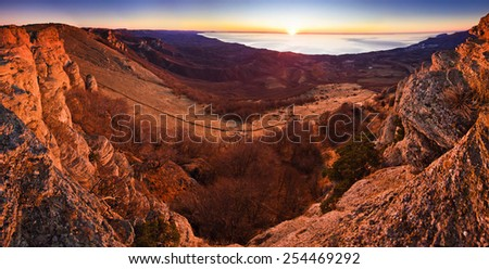 aerial view from mountains with trees of magnificent colored sunrise above the sea with forest on hills  - stock photo