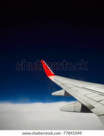 Aerial view from plane with wing and deep blue clear sky - stock photo