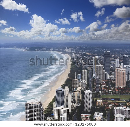aerial view from Surfer's paradise Q1 skyscrapers on the city building towers, coastline with sand, surf and beach under blue sky