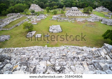 Aerial view from the top of ancient Mayan pyramid to ruins of city and jungles - stock photo