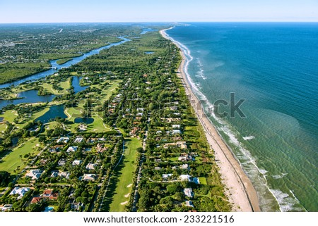 aerial view looking north, of Jupiter and Hobe Sound, Florida, along the Atlantic Ocean coast, lined by the beach and dotted by luxury homes golf courses - stock photo