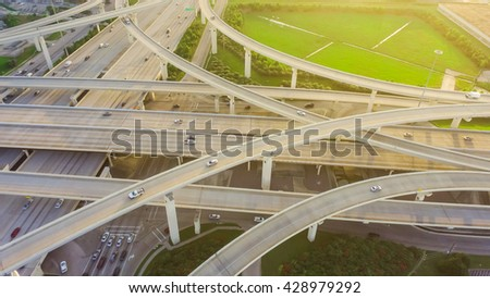 Aerial view massive highway intersection, stack interchange with elevated road junction overpass at late afternoon in Houston, Texas. This five-level freeway interchange carry heavy traffic, panorama.