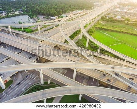 Aerial view massive highway intersection, stack interchange with elevated road junction overpass at late afternoon in Houston, Texas. This five-level freeway interchange carry heavy rush hour traffic.