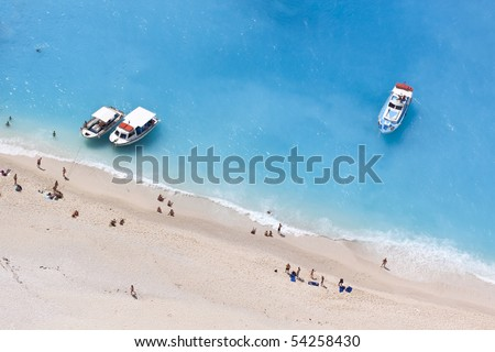 aerial view of a beach with some motorboats and some people swimming in the turquoise sea.