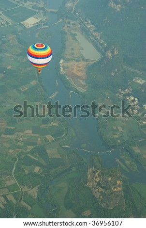 Aerial view of a colourful hot air balloon flying over a river in the countryside near YangShuo, Guangxi province, China. - stock photo