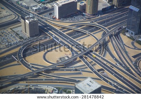 Aerial view of a complex highway overpass in Dubai, UAE. Modern busy city, downtown during the day. Hight contrast color.
