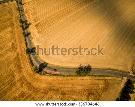 Aerial view of a country road amid fields with a red car - stock photo