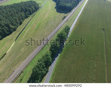 aerial view of a country road next to a railway line in the countryside