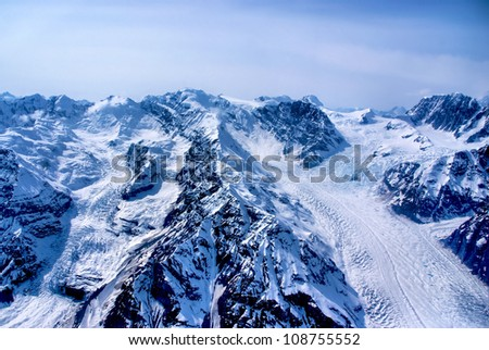 Aerial View of a Craggy Alaskan Mountain Peak with the Forming Headwaters of a Glacier in the Great Alaskan Wilderness, Denali National Park, Alaska.  A Beautiful Snowscape of Rock, Snow, and Ice. - stock photo