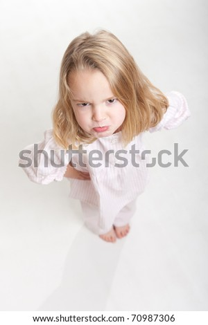 Aerial view of a cute little blonde girl with an angry expression in her pajamas - stock photo