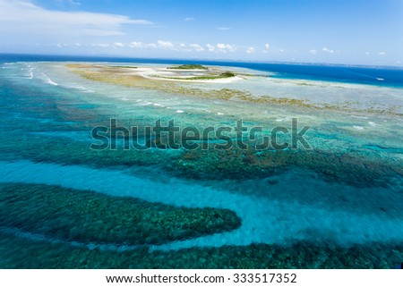 Aerial view of a deserted tropical island and coral reef lagoon of an atoll, Okinawa, Japan - stock photo