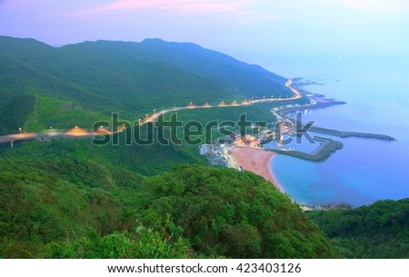 Aerial view of a fishing village at dawn on northern coast of Taipei Taiwan ~ Magnificent scenery of a coastal highway along beautiful coastline and a fishing village bathed in gloomy blue twilight~ - stock photo
