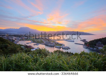 Aerial view of a fishing village at dawn on northern coast of Taipei Taiwan ~ Sunrise scenery of a fishing port and beautiful coastline in norther Taiwan - stock photo