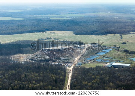 Aerial view of a gigantic hill of garbage contrasted with a green, unspoiled landscape around near Moscow, Russia - stock photo