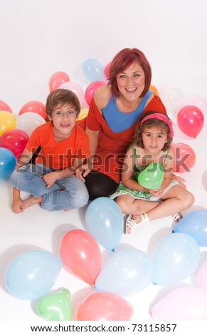Aerial view of a mom with boy and girl playing with colourful balloons - stock photo