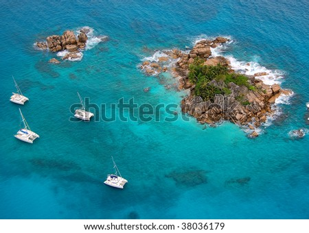 Aerial view of a paradise island with a few boats around - stock photo