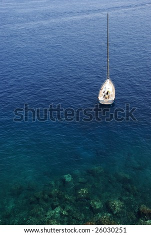 Aerial view of a sailboat in the transparent water of Aeolian islands, Sicily, Italy. - stock photo
