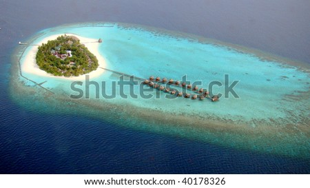 Aerial view of a small island and water villas, Maldives - stock photo