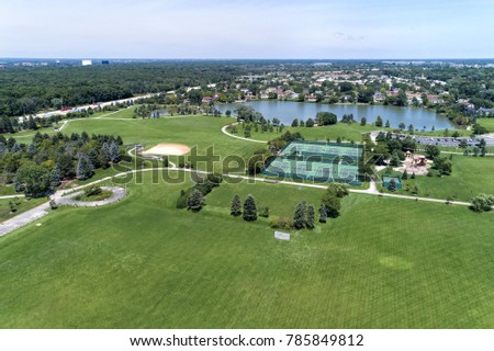 Aerial view of a suburban park district area with a soccer field, tennis courts, lake and playground in Northbrook, IL. USA