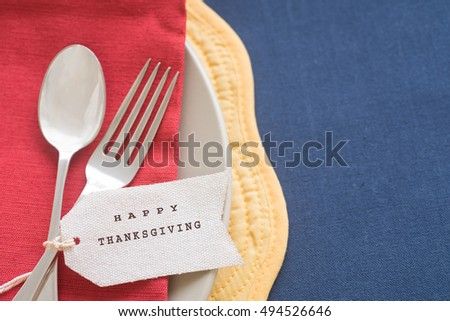 Aerial View of a Table Place setting with fork, spoon, red napkin, white plate, yellow mat, blue cloth, and white name tag with Happy Thanksgiving wishes printed. Horizontal with bright, natural tones