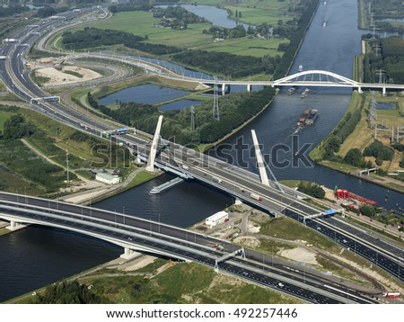 Aerial view of a three bridges over the canakl Amsterdam-Rijnkanaal in Amsterdam Zuidoost. First the new bridge on highway A1. Next to it is the old freeway bridge and in the back the railroad bridge.