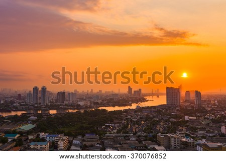 Aerial view of Bangkok city night light at Chao Phaya riverfront and bridge across the river with central business district. - stock photo