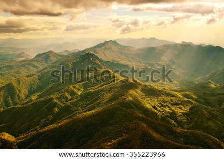 Aerial view of beautiful mountain range with warm sunlight during flight from Mae Hong Son province to Chiang Mai province, northern part of Thailand. - stock photo
