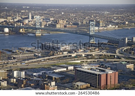 Aerial view of Ben Franklin bridge crossing the Delaware River from Philadelphia, Pennsylvania side into Camden New Jersey - stock photo