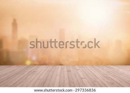 Aerial view of blurred abstract background of morning sunrise with flare from the kitchen balcony with wood floor in sepia brown color tone: Wooden table with blur cityscape view with gold light   - stock photo