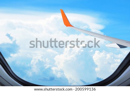 Aerial view of clouds & sky from window of the airplane - stock photo