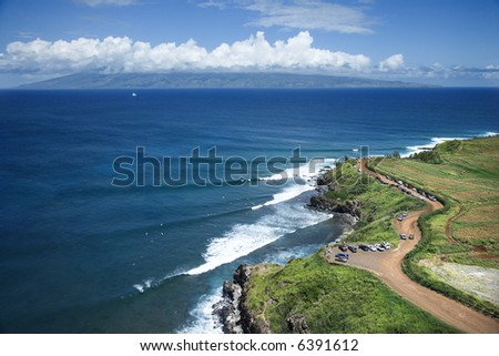 Aerial view of coastline with surfers and parked cars on Maui, Hawaii. - stock photo