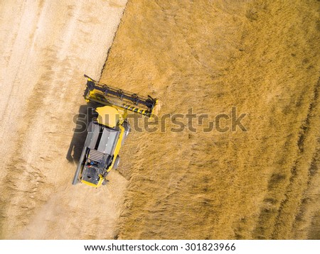 Aerial view of combine harvester on wheat field. Industrial backround on agricultural theme. - stock photo