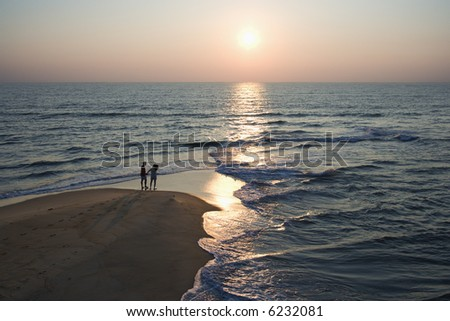 Aerial view of couple on beach in Bald Head Island, North Carolina during sunset. - stock photo