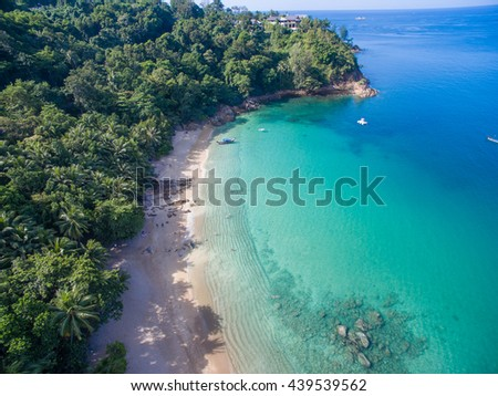Aerial view of cozy white sand beach with turquoise clear sea water, and one traditional longtail boat. Banana Beach, Phuket, Thailand.