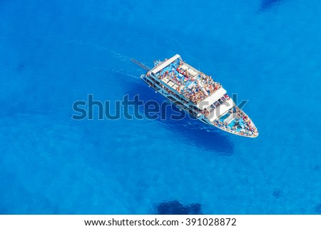 Aerial view of cruise boat in azure sea - stock photo