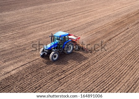 Aerial view of cultivated land tractors - stock photo