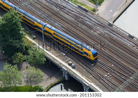 Aerial view of Dutch train at a bridge crossing a canal - stock photo