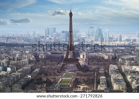 aerial view of eiffel tower on bright day with blue sky and fluffy clouds. La Defense brightly lit in background.