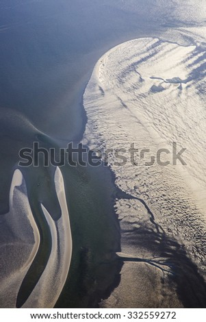 aerial view of estuary mudflat wetland of the shore of Ameland island in the reflecting sunset, The Netherlands - stock photo