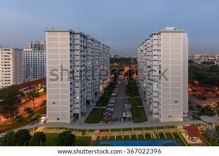 Aerial view of Eunos neighborhood in Singapore at blue hour. The new estate HDB housing complex with outdoor tennis and basketball court, car park, and green garden at the center. Vintage filter look - stock photo