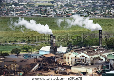 Aerial view of  factory smokestacks spouting white clouds on Maui, Hawaii.
