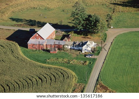 Aerial view of farmhouse and fields - stock photo