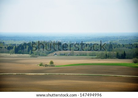 Aerial view of farmland and woods behind it - stock photo