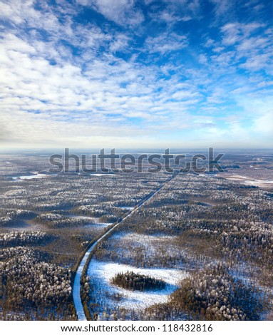 Aerial view of forest of plain and country road during a winter day. - stock photo