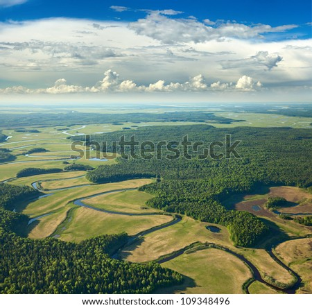 Aerial view of forest river over the summer woodlands during a flight. - stock photo