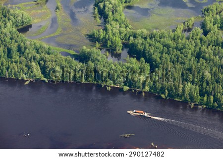 Aerial view of forest the river during summer day. The ship with barge moves along the river. The refueler is on the barge. - stock photo