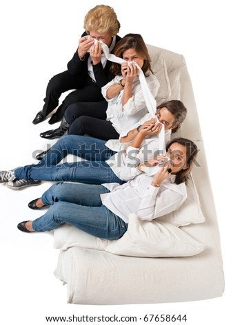 Aerial view of four crying women of different ages on a white sofa - stock photo