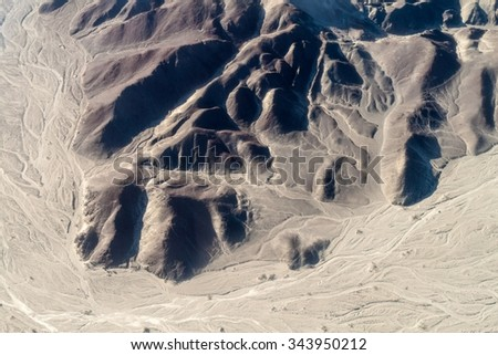 Aerial view of geoglyphs near Nazca - famous Nazca Lines, Peru. On the bottom, small Astronaut figure is present. - stock photo