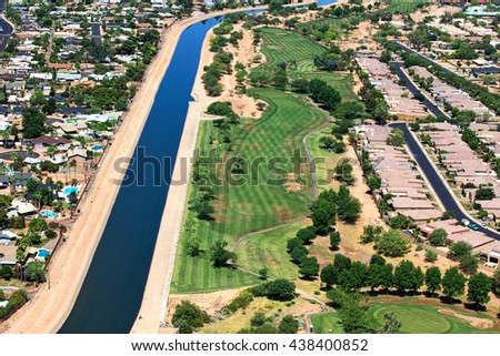 Aerial view of golf course along a large irrigation canal and residential neighborhood - stock photo