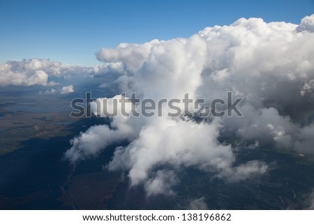 Aerial view of great clouds which float over the flood-land of river during a flight in summer. - stock photo